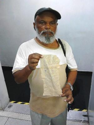 Idoso segura carta escrita em papel de pão para jovem americana (Foto: Rodrigo Nardelli/ G1)