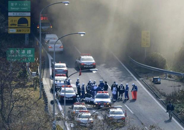 Viaturas policiais estacionam enquanto fumaça sai do túnel de Sasago neste domingo (2) (Foto: AP)
