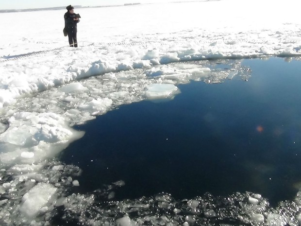 Pessoa pbserva buraco provocado por meteorito em lago congelado Chebarkul na Rússia. (Foto: AP)