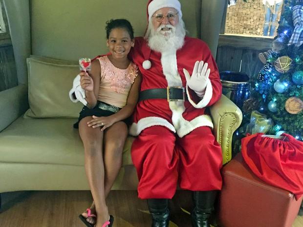 Papai Noel entrega guloseima para criança em shopping da Asa Norte, em Brasília (Foto: Jéssica Nascimento/G1)