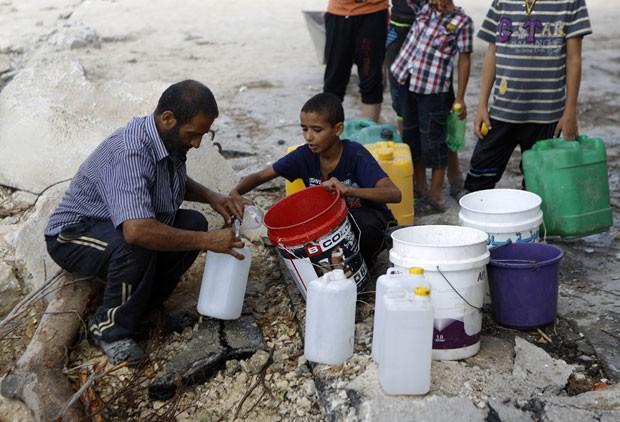 Palestinos enchem recipientes com água na cidade de Gaza nesta quarta-feira (6), em meio a trégua com Israel (Foto: Mohammed Abed/AFP)