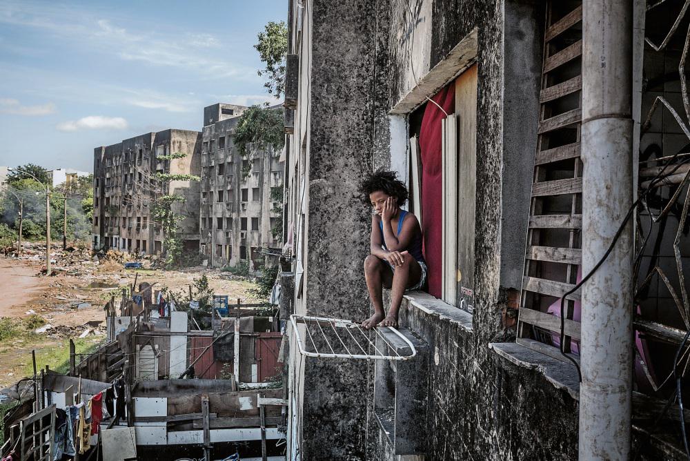 Sentada no parapeito da janela,observa a rua.Ela vive com os sete irmãos num dos apartamentos dos cinco edifícios inacabados (Foto:  Peter Bauza)