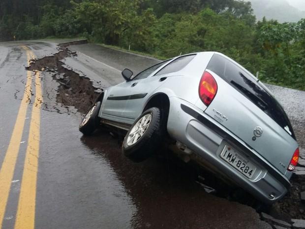 Asfalto cede devido à chuva e carro cai em buraco (Foto: Divulgação/PRF)