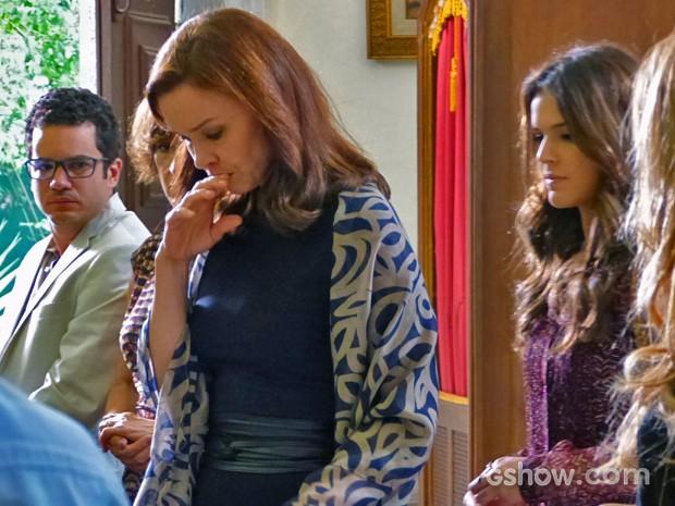 Sem jeito, Helena repara que todos estão falando sobre ela (Foto: Em Família/TV Globo)