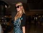 Paris Hilton usa vestido com fenda em viagem e exibe pernas