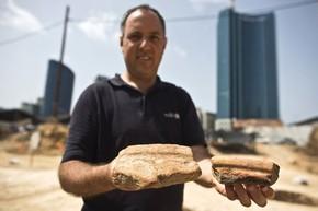 Diego Barkan exibe pedaços de vasilhas egípcias usadas para fabricar cerveja encontradas em escavações (Foto: Nir Elias/Reuters)