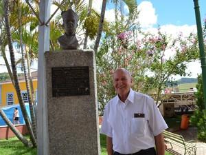 Felipe Bardoglio ao lado do busto do monsenhor Nagel, em Aiuruoca (Foto: Samantha Silva/G1)