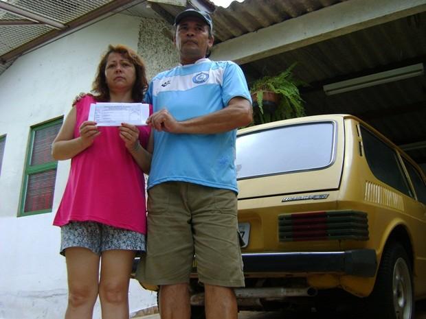 Marli e Florisvaldo com carnê de IPTU em frente de casa (Foto: Alan Schneider / G1 Bauru e Marília)