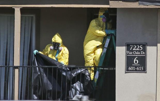 Funcionários de empresa de limpeza trabalham em apartamento onde paciente diagnosticado com ebola nos EUA estava hospedado  (Foto: AP Photo/LM Otero)