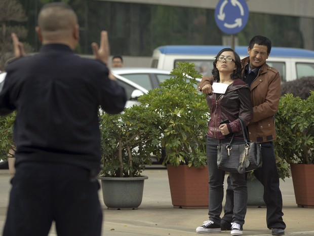 Homem mantém mulher refém na cidade de Kunming, na China, usando um cutelo, enquanto policial tenta dissuadi-lo (Foto: Reuters)