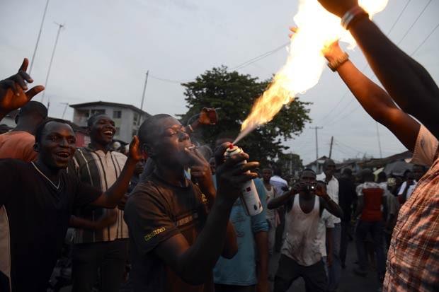 Homem usa um cigarro para disparar um spray e usá-lo como maçarico jogando chamas ao céu em Kano, durante festa pelo resultado da eleição (Foto: Pius Utomi Ekpei/AFP)
