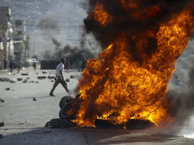 Protestos tomam ruas do Haiti contra falta de água, luz e baixos salários (Foto: HECTOR RETAMAL / AFP)