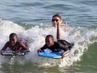 Filhos de Madonna se divertem pegando onda em praia do Rio