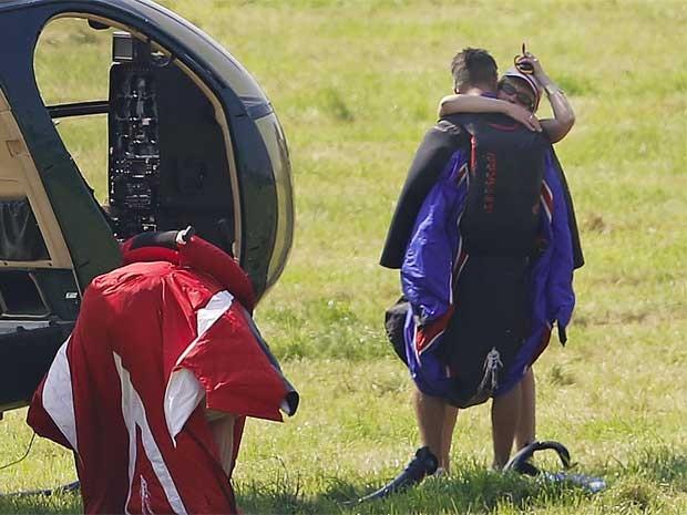 O dublê Gary Connery abraça sua mulher Vivienne antes de embarcar um helicóptero e pular da aeronave a 731 metros de altura, aterrissando sem o uso de pára-quedas, em Henley-on-Thames, oeste de Londres, nesta quarta-feira (23) (Foto: Reuters)