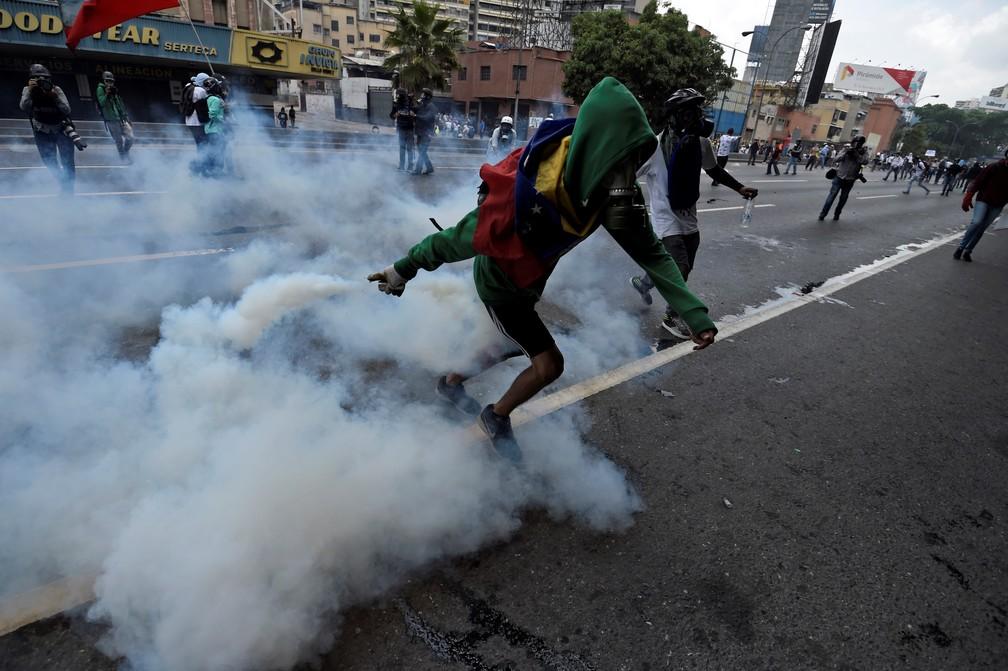 Manifestantes e polícia se enfrentam durante manifestação nesta quarta-feira (19) em Caracas (Foto: JUAN BARRETO / AFP)