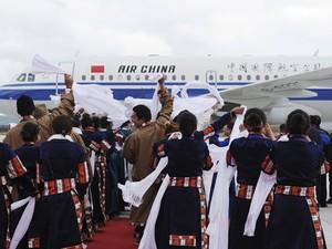 Cidadãos usando roupas típicas tibetanas acenam para os passageiros do primeiro voo no aeroporto (Foto: Reuters/China Daily)