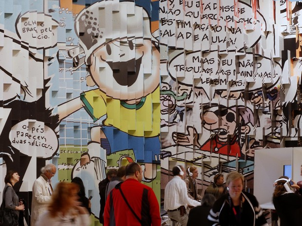 Painel com desenho do Menino Maluquinho, personagem de Ziraldo, é observado pelo público na Feira de Frankfurt (Foto: AP/Michael Probst)
