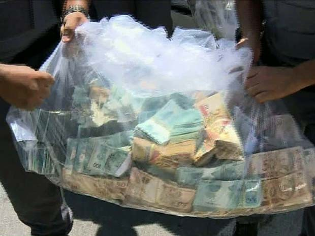 Policiais levam sacola de dinheiro apreendido em operação do MP em Indaiatuba (Foto: Reprodução / EPTV)
