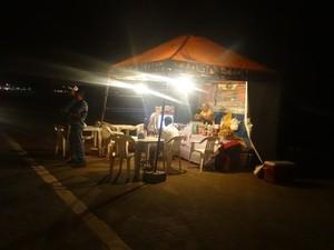Única iluminação da avenida vem das barracas (Foto: Nívio Dorta/G1)