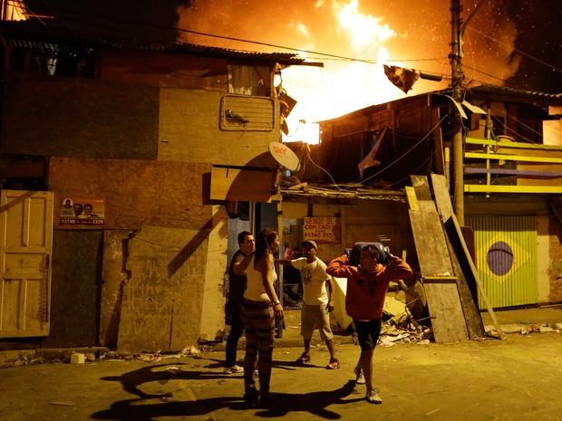Moradores entraram em desespero durante um incêndio de grandes proporções que atingiu uma favela no Campo Belo, Zona Sul de São Paulo, durante a noite de domingo. Na foto, um deles remove um botijão para evitar o risco de explosão (Foto: Nelson Antoine/Frame/Estadão Conteúdo)