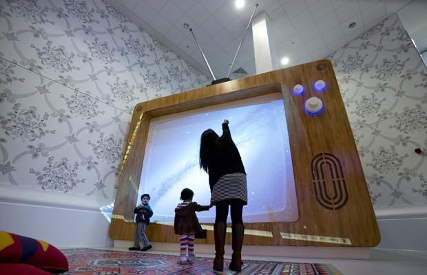 Uma televisão gigante também faz parte do setor. 'Precisávamos criar espaços para permitir que as crianças não ficassem confinadas nas camas de hospital e para facilitar o ambiente de recuperação', disse Siobhan Carr, consultora pediátrica (Foto: Neil Hall/Reuters)