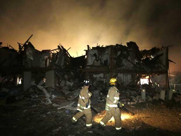 Bombeiros verificam um prédio destruído perto da companhia. (Foto: LM Otero / AP Photo)