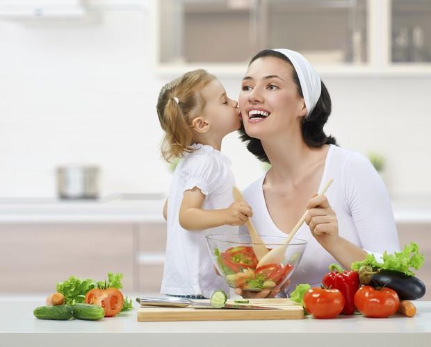 Mãe cozinha com a filha criança (Foto: Thinkstock)