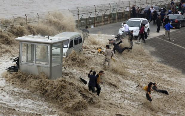 Grupo é atingido onda às margens do rio Qiantang, em Hangzhou (Foto: China Daily/Reuters)