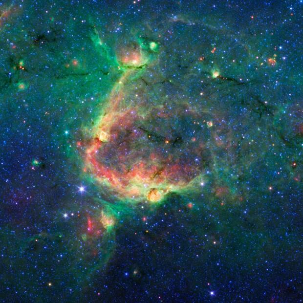 Bolha gigante esculpida na poeira espacial por estrelas de grande massa provoca a formação de bolhas menores (Foto: Nasa/JPL-Caltech/University of Wisconsin )