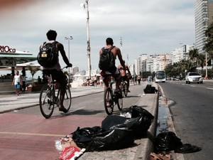 Apesar do trabalho dos garis nesta sexta, alguns sacos de lixo ainda dividiam o espaço com ciclistas na orla de Copacabana, altura do posto 5 às 10h. (Foto: Guilherme Brito / G1)