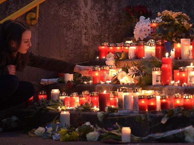 Aluna coloca velas em homenagem aos estudantes da escola Joseph-Koenig em Haltern, oeste da Alemanha, que morreram no acidente aéreo na França (Foto: Martin Meissner/AP)