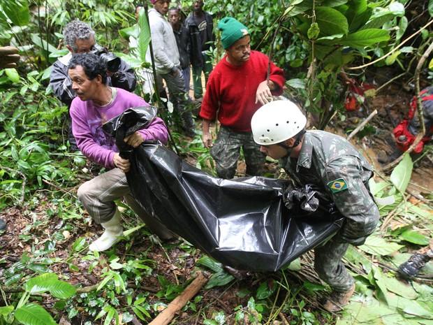 José Ventura (à esquerda) ajuda bombeiros a resgatar o corpo  do sobrinho Nicolas em Petrópolis (Foto: Marcos de Paula/Estadão Conteúdo)