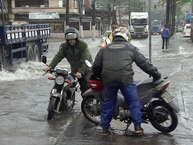 Motoristas e pedestres têm dificuldades para enfrentar ruas alagadas no litoral de SP (Foto: Reprodução/TV Tribuna)