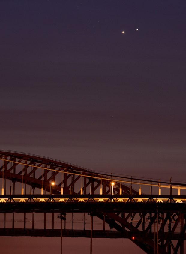 Aproximação dos planetas no céu foi fotografada perto das pontes de Hell Gate (atrás) e Robert F. Kennedy (frente), em Nova York (Foto: Stan Honda/AFP)