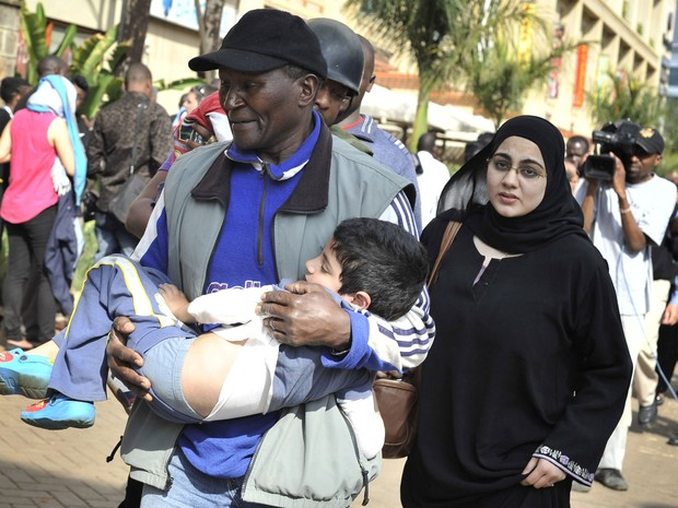Trabalhador do resgate socorre uma criança após tiroteio em shopping em Nairóbi (Foto: Riccardo Gangale/AP)