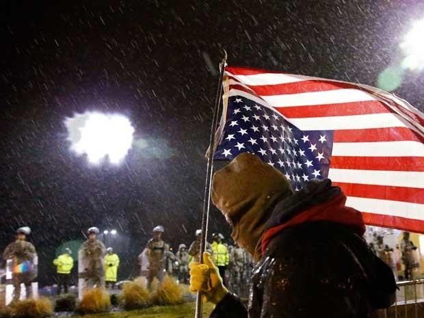 Manifestante marcha na frente da guarda nacional, em Ferguson. (Foto: Jim Young / Reuters)