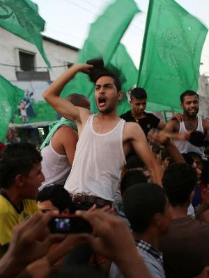 26/08 - Palestinos comemoram cessar-fogo por prazo indeterminado na Faixa de Gaza (Foto: Said Khatib/AFP)