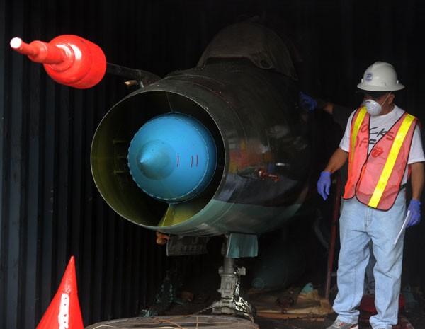 Homem trabalha em contâiner que tem o avião MIG-21 encontrado em barco norte-coreano. (Foto: Rodrigo Arangua/AFP PHOTO)