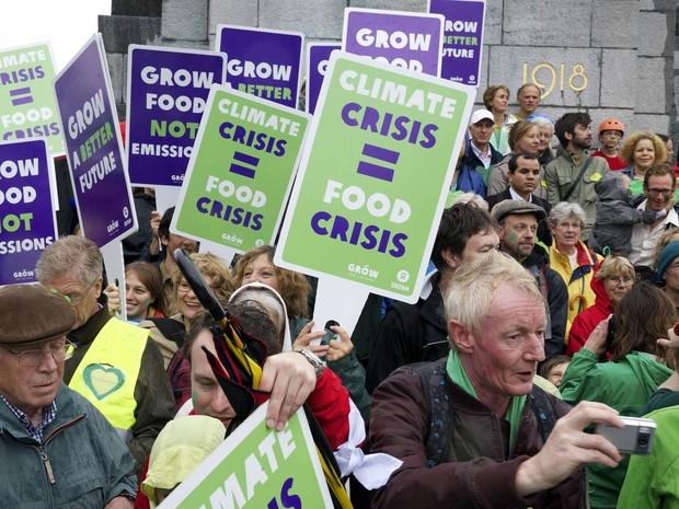 Casal mostra cartazes a favor de políticas pelo desenvolvimento sustentável durante Marcha Popular pelo Clima em Bruxelas, na Bélgica (Foto: Belga Nicolas Maeterlinck/AFP)