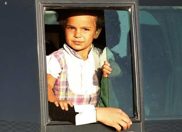 Menina refugiada síria em ônibus ao chegar a parada próximo à cidade de Reyhanli, na fronteira turca, nesta quinta-feira (9) (Foto: AFP)