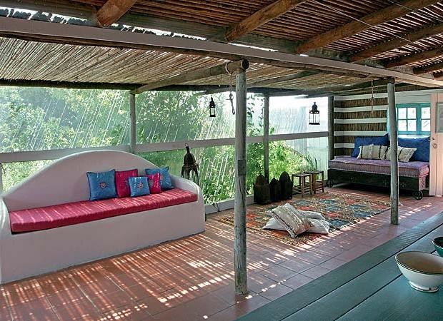 Uma sala de estar externa foi criada junto à casa, com mesa de jantar que reúne os amigos e a família. Ao fundo, o sofá com base de ferro foi feito sob medida em Tânger. À esq., simplicidade acolhedora no sofá branco de alvenaria. Peças marroquinas, como  (Foto: Casa e Jardim)
