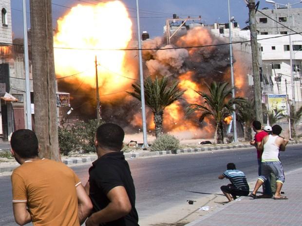 Palestinos observam de perto a explosão de um ataque aéreo israelense a uma casa na Cidade de Gaza (Foto: Roberto Schmidt/AFP)
