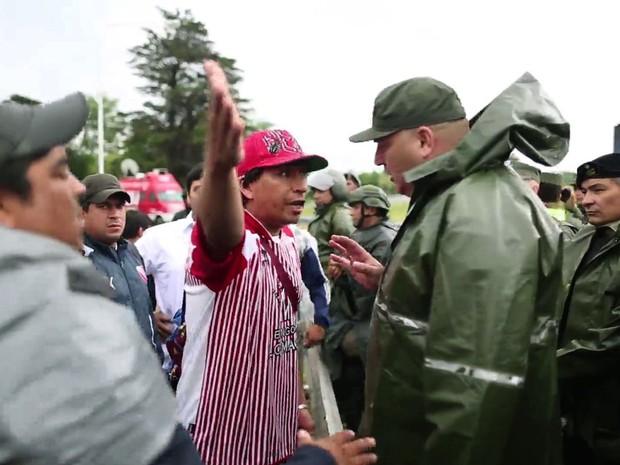 Policial discute com trabalhadores de empresa avícola que bloquearam a principal entrada do aeroporto internacional Ezeiza, em Buenos Aires, na terça (22) (Foto: AFP Photo/AFPTV – Anibal Greco)