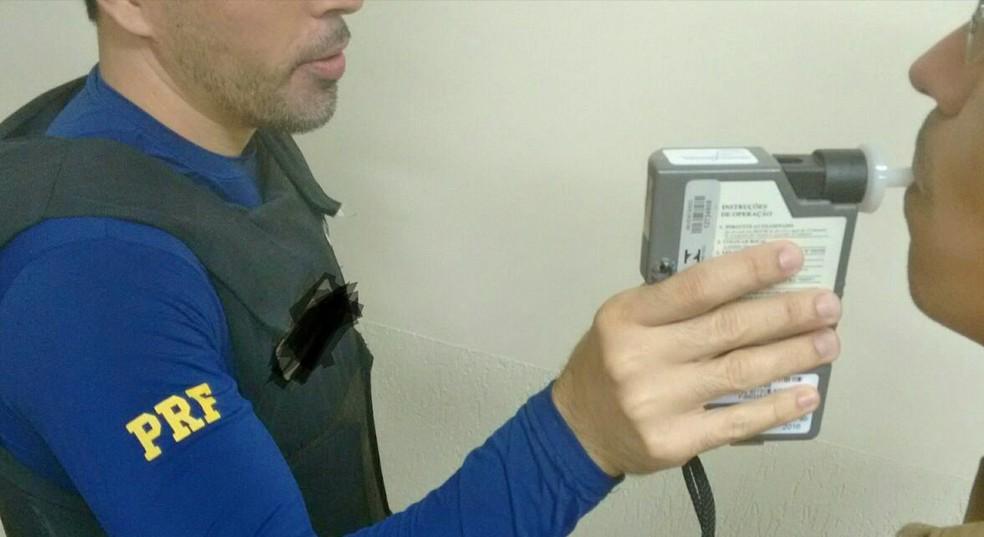 Agente da PRF faz exame do bafômetro em motorista (Foto: Divulgação/PRF-AC)