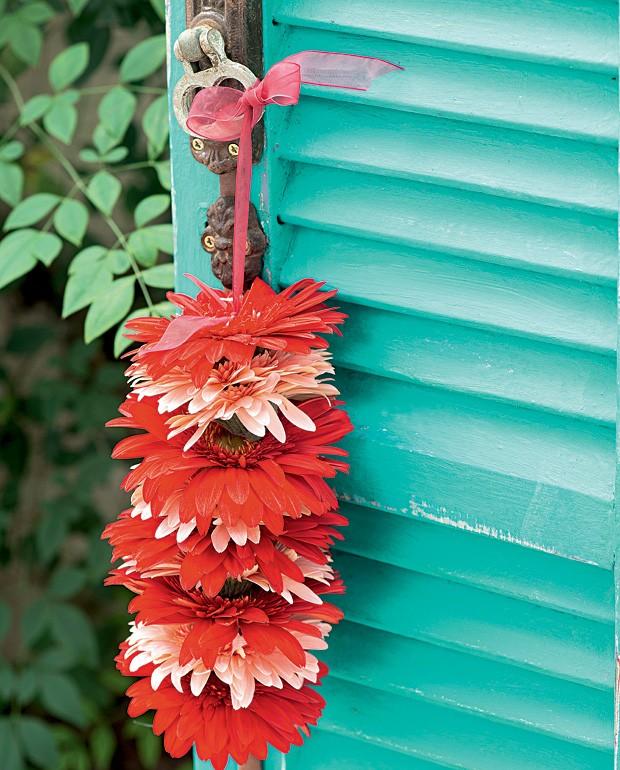 Flores animam qualquer cantinho. Nesse caso, foram colocadas em uma fita pendurada na maçaneta da porta. Pode abusar das cores sem medo: uma porta azul pode ficar incrível com um detalhe vermelho. (Foto: Iara Venanzi/Casa e Comida)