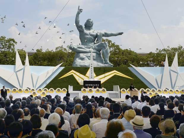 Pombos sobrevoam a Estátua da Paz em Nagasaki, durante cerimônia em comemoração ao 70º aniversário do bombardeio da cidade (Foto: Kyodo / via Reuters)