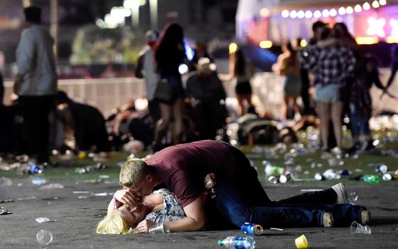 Um homem deita-se sobre mulher durante ataque de atirador (Foto: David Becker/Getty Images)
