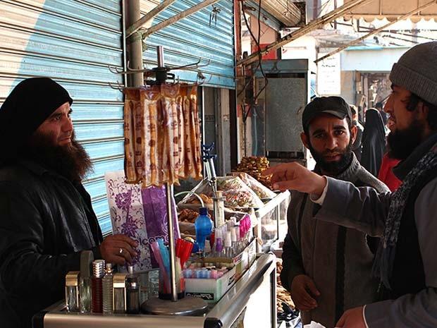 Jihadista do Estado Islâmico (direita) conversa com vendedor de perfume em rua da Raqqa, na Síria, em foto de setembro de 2014 (Foto: Militant website via AP)