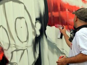 Grafiteiro faz desenho em tapume de obras do Aeroporto de Viracopos em Campinas (Foto: Lana Torres/G1Campinas)