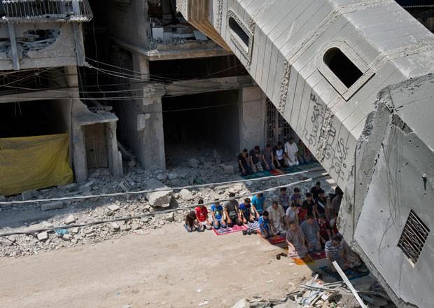 Palestinos durante orações perto de mesquita destruída em Gaza (Foto: Roberto Schmidt/AFP)